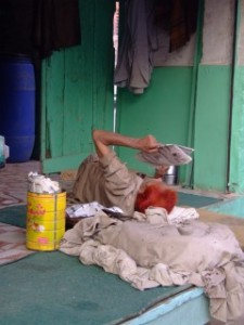 Henna dyed man reading a paper in Pakistan