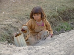 Young Afghan refugee girl playing in the dirt