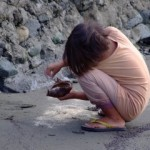 Girl playing with coconut and sand on the beach
