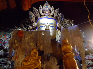 Statue of Buddha peeking out from behind some silk scarves in Tibet