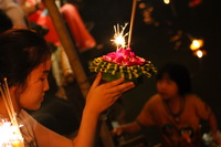Girl praying at Loi Krathong while another girl helps others in the background