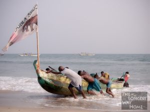 Ghanaians heaving a fishing boat onto a beach