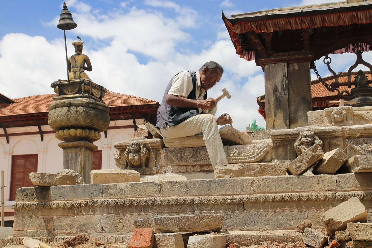Stone mason working on restoring the Vatsala Durga temple in Bhaktapur Nepal